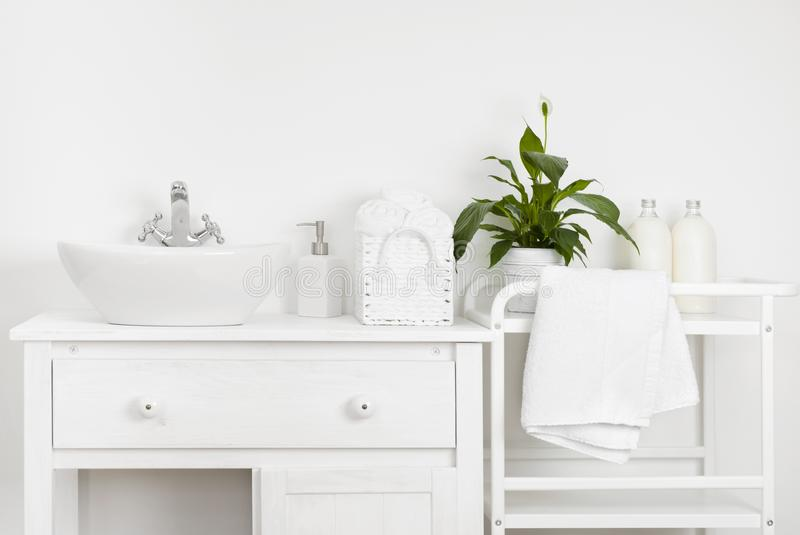 Interior compacto del cuarto de baño con los muebles, el estante, las toallas y el fregadero blancos del vintage foto de archivo libre de regalías