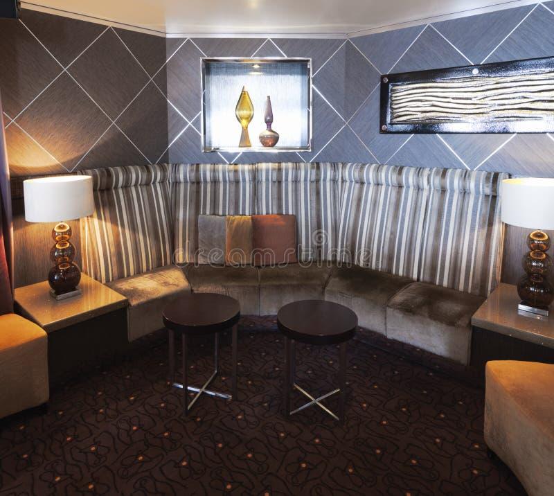 interior con diseño moderno y elegante con la esquina del sofá con los amortiguadores y las sillas contemporáneas bajas imagen de archivo libre de regalías