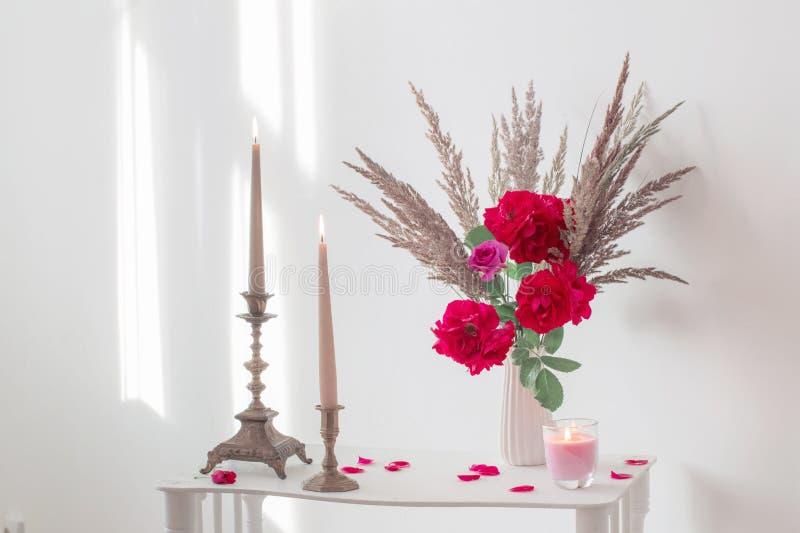 interior con el ramo de rosas y de velas ardientes fotos de archivo libres de regalías