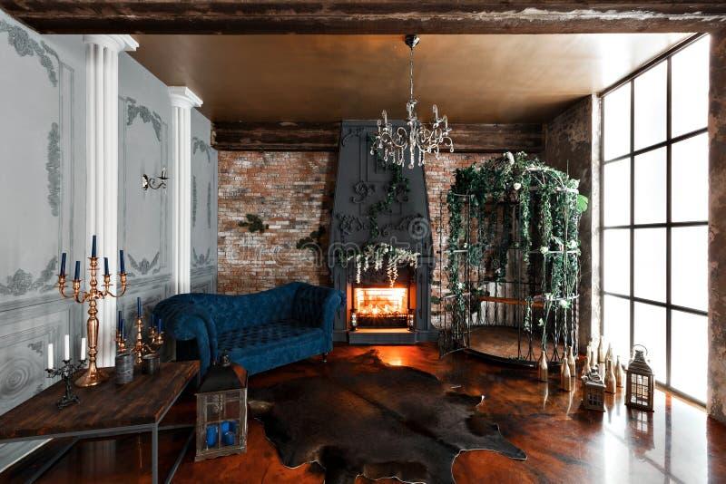 Interior con la chimenea, las velas, la piel de vacas, la pared de ladrillo, la ventana grande y una célula del metal de un desvá imagenes de archivo