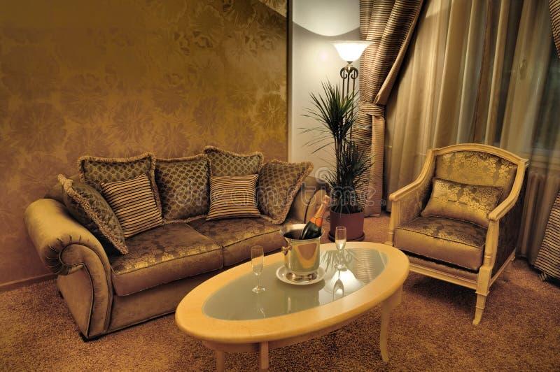 Interior con muebles con estilo y vino espumoso foto de archivo libre de regalías