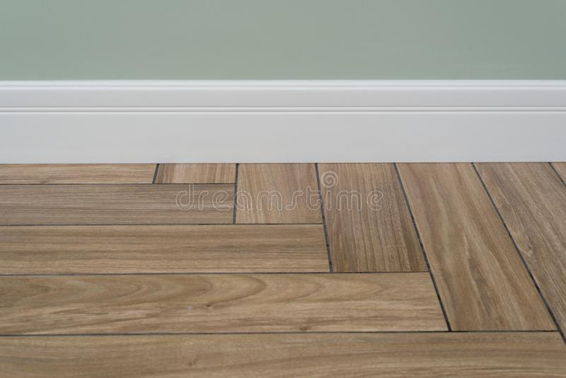 Interior concept. Light matte wall, white baseboard and tiles immitating hardwood flooring. Oak wood texture of floor with tiles immitating hardwood flooring royalty free stock photo