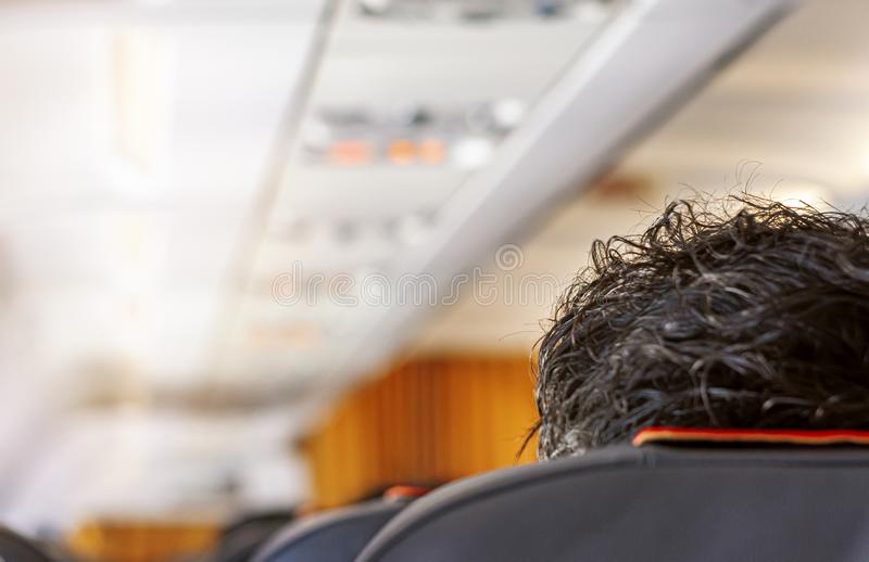 Interior of the corridor of an airplane with a passenger`s head with thick black hair. Concept of travel and mode of transport stock photography