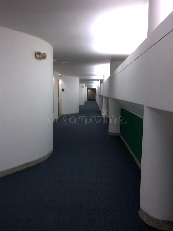 Interior corridor of modern building with striking curves and blue carpet. stock images