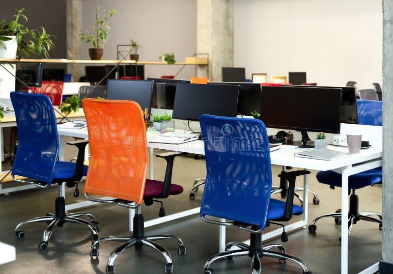 Interior creativo del espacio de co-trabajo acogedor con los ordenadores fotografía de archivo