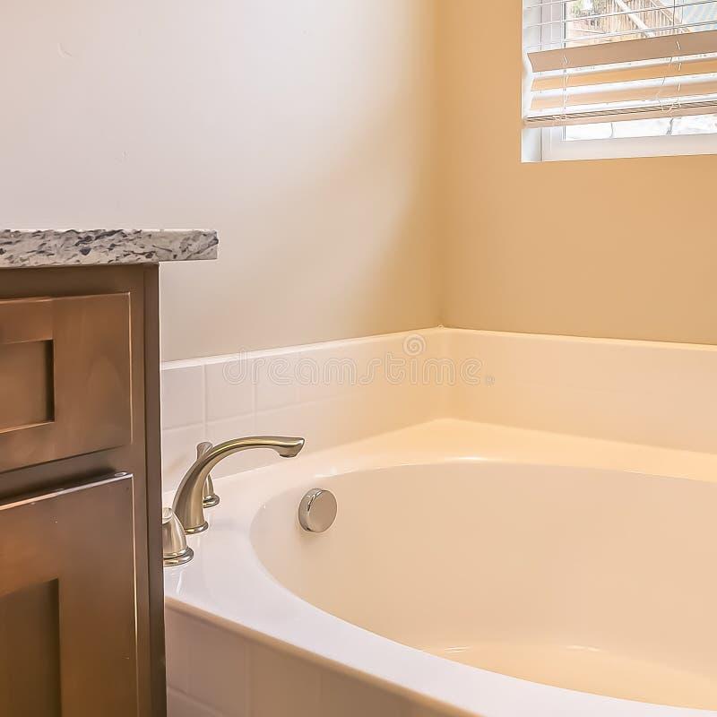 Interior cuadrado del cuarto de baño del marco con la bañera oval contra la pared y la ventana blancas con las persianas foto de archivo libre de regalías