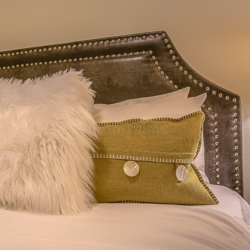 Interior cuadrado del dormitorio del marco con las almohadas contra el cabecero tapizado del belgrave de una cama fotos de archivo libres de regalías