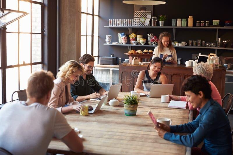 Interior da cafetaria com os clientes que usam dispositivos de Digitas fotografia de stock royalty free
