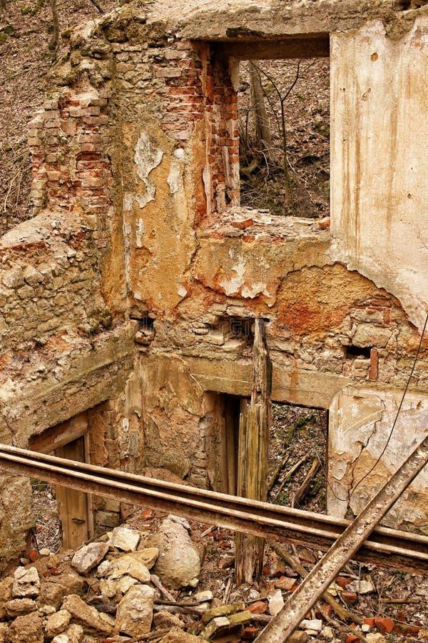 Interior da casa arruinada com paredes de tijolo e trilhos do metal imagem de stock royalty free