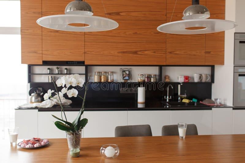 Interior da casa com cozinha de plano aberto, sala de estar e espaço para refeições Luzes modernas e tabela de madeira imagem de stock royalty free