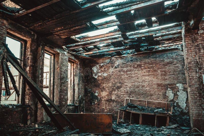 Interior da casa do tijolo queimado com mobília queimada, sala de construção arruinada após o fogo para dentro foto de stock royalty free