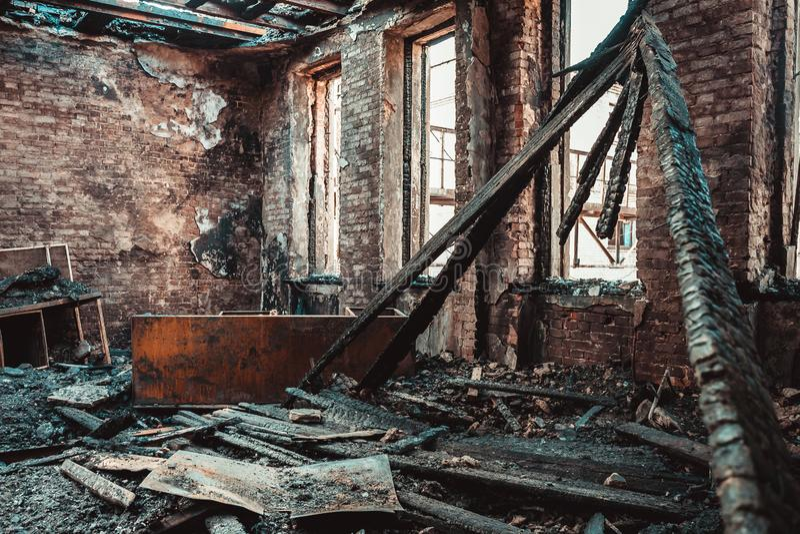 Interior da casa do tijolo queimado com mobília queimada, sala de construção arruinada após o fogo para dentro imagem de stock royalty free