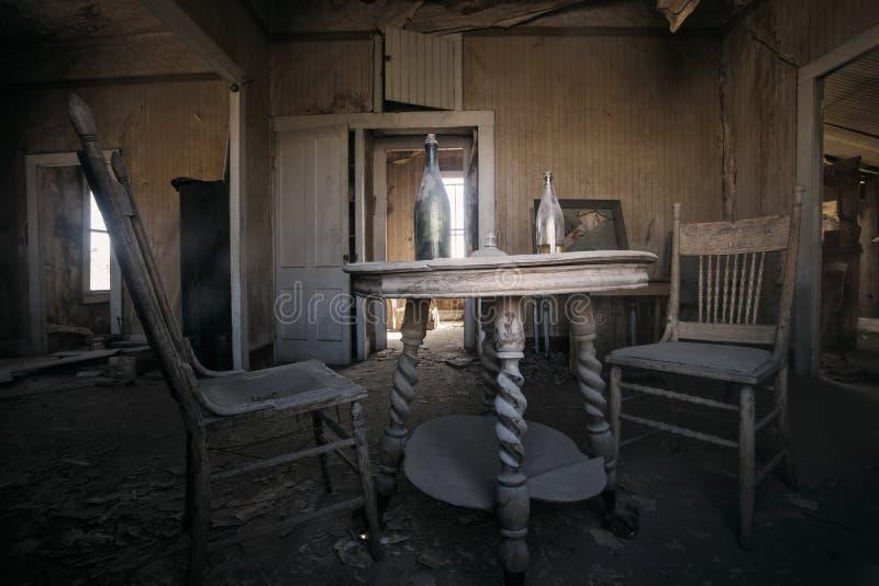 Interior da construção ocidental velha abandonada com as duas cadeiras e tabelas velhas imagens de stock