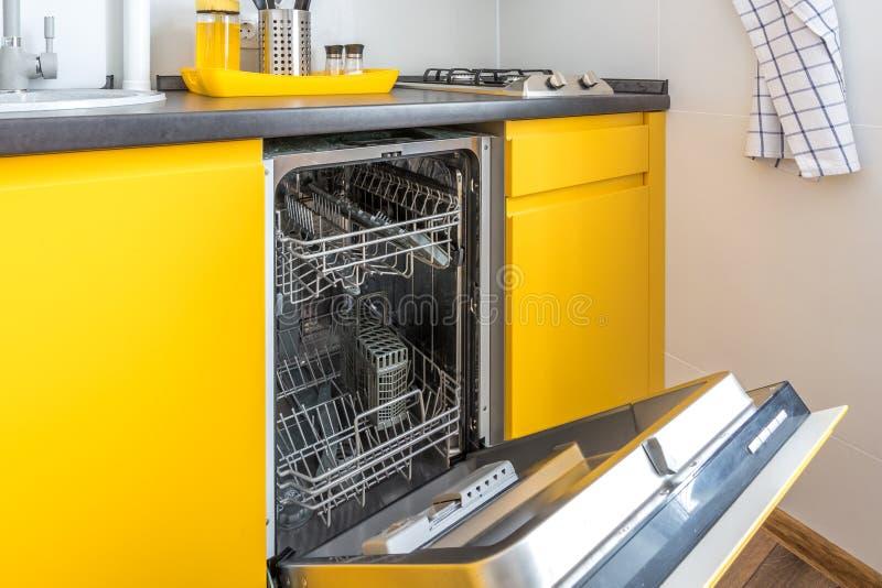 Interior da cozinha moderna com a máquina de lavar louça aberta no apartamento liso do sótão no estilo minimalistic com cor amare fotografia de stock
