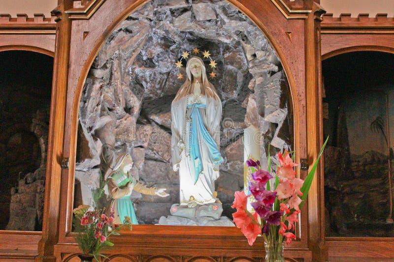 Interior da igreja, detalhe à estátua de Madonna com flores fotografia de stock royalty free