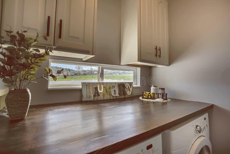 Interior da lavandaria com armários e janela acima da bancada de madeira marrom imagens de stock royalty free