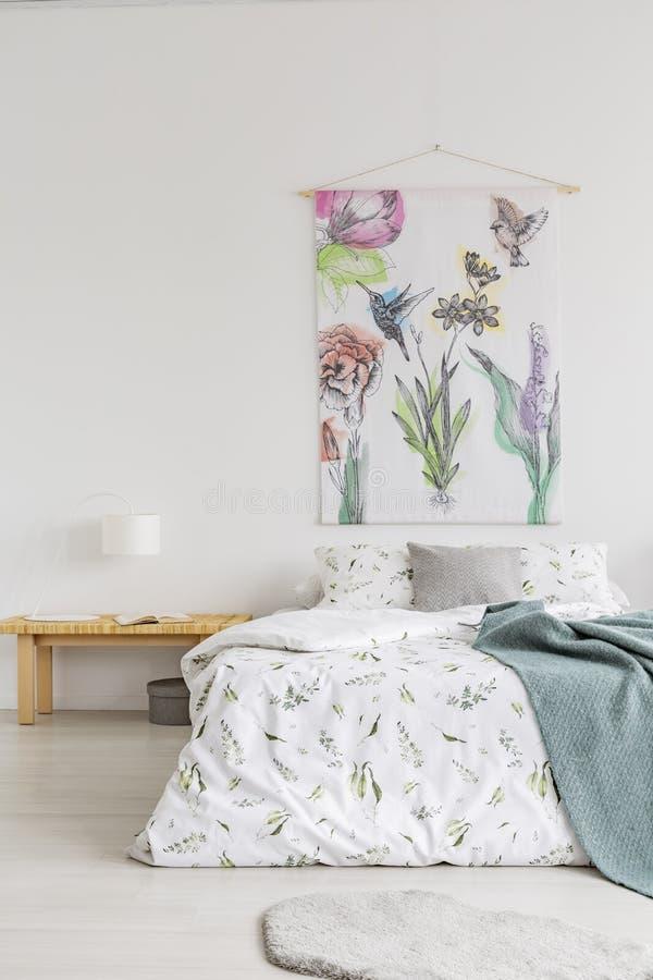Interior da sala branca com cama de casal, tabela de cabeceira de madeira com lâmpada e livro e pintura do material que pendura n imagens de stock
