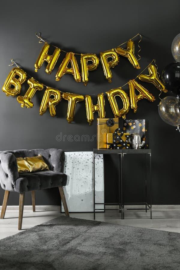 Interior da sala com as caixas de presente e o FELIZ ANIVERSARIO da frase feitos de letras do balão imagens de stock royalty free