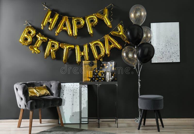 Interior da sala com as caixas de presente e o FELIZ ANIVERSARIO da frase feitos de letras do balão imagem de stock royalty free