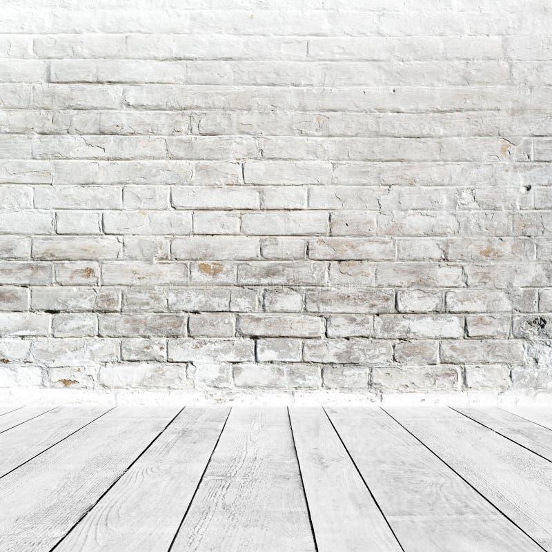 Interior da sala com a parede de tijolo e o assoalho brancos da madeira imagens de stock