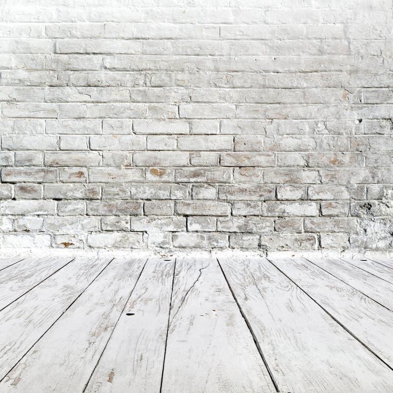 Interior da sala com a parede de tijolo e o assoalho brancos da madeira fotografia de stock