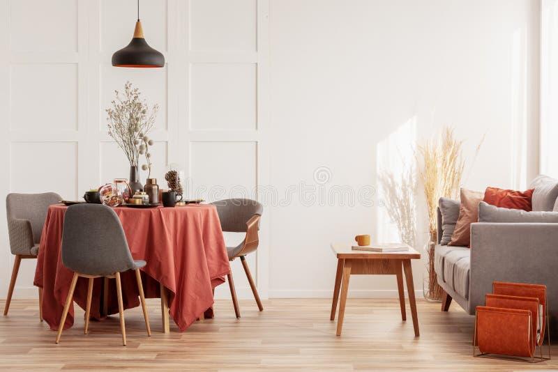 Interior da sala de estar e jantar com sofá cinza e mesa coberta de toalha laranja fotos de stock
