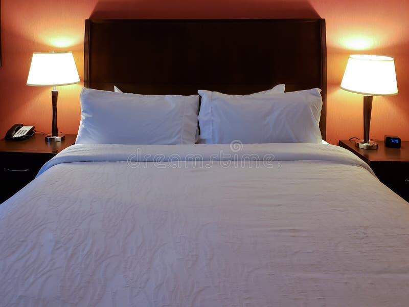 Interior da sala de hotel com cama feita e descansos com lâmpadas sobre e uma parede vermelha fotos de stock royalty free