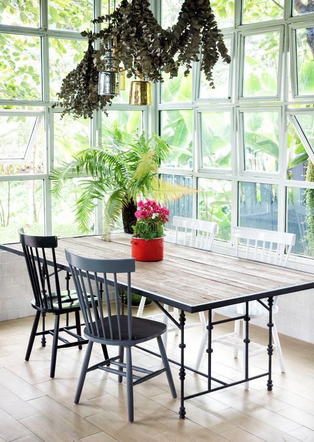 Interior da sala de jantar com tabela, cadeiras e plantas contra w grande fotos de stock