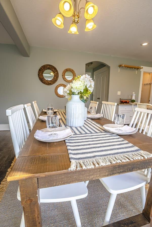 Interior da sala de jantar de uma casa com a tabela de madeira marrom e as cadeiras brancas foto de stock