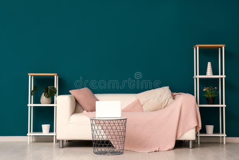 Interior da sala de visitas com o sofá confortável à moda perto da parede da cor fotografia de stock royalty free