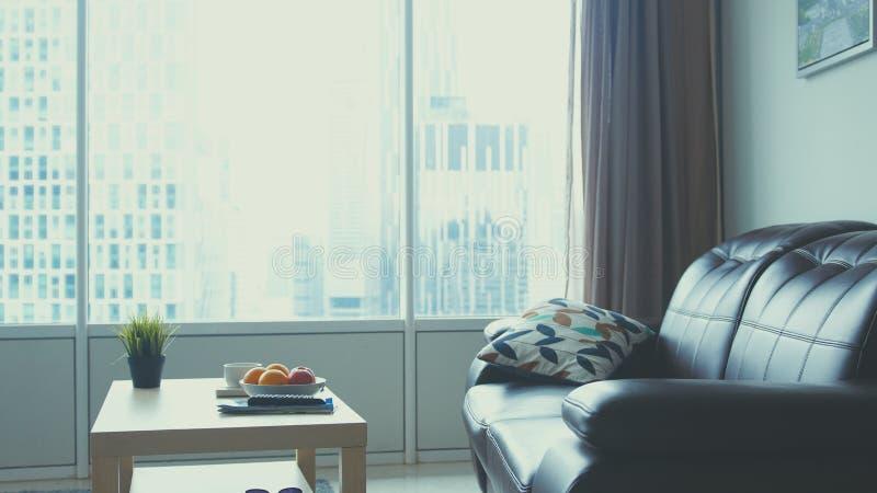 Interior da sala de visitas do projeto moderno com opinião da arquitetura da cidade e sofá de couro pela janela imagens de stock royalty free