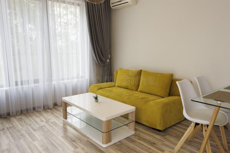 Interior da sala de visitas moderna com o sofá amarelo confortável e as grandes janelas fotografia de stock royalty free