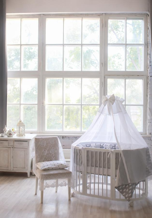 Interior da sala do ` s das crianças, estilo de Provence, berço de bebê oval, com dossel, interior da luz, grande janela bonita imagens de stock royalty free