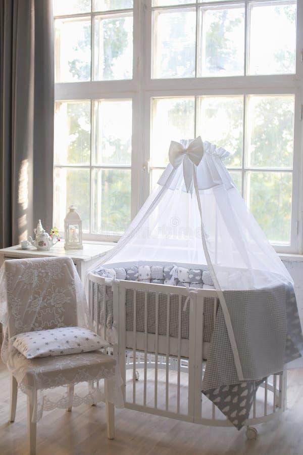 Interior da sala do ` s das crianças, estilo de Provence, berço de bebê oval, com dossel, interior da luz, grande janela bonita fotos de stock royalty free