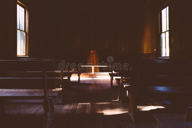 Interior of a dark wooden Christian church with a cross on the stand in the countryside. The interior of a dark wooden Christian church with a cross on the stand stock photos