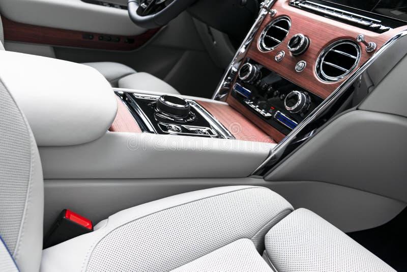Interior de couro branco do carro luxuoso moderno com o painel de madeira natural Parte dos detalhes de couro do banco de carro c foto de stock