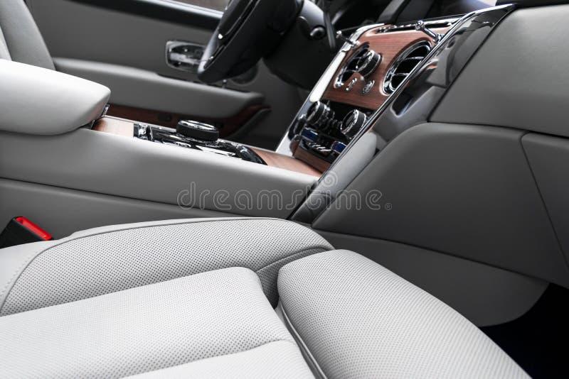 Interior de couro branco do carro luxuoso moderno com o painel de madeira natural Parte dos detalhes de couro do banco de carro c imagens de stock