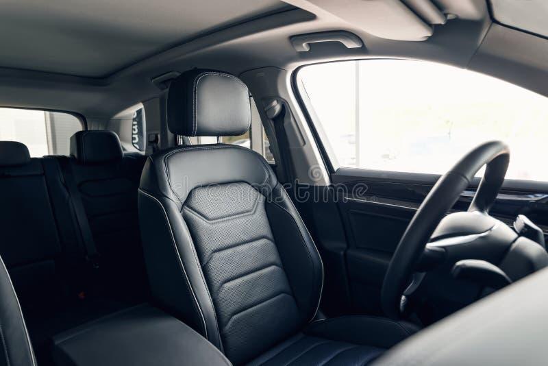 Interior de cuero negro del coche Tablero de instrumentos del coche moderno y volante interiores Interior de cuero perforado del  imagenes de archivo