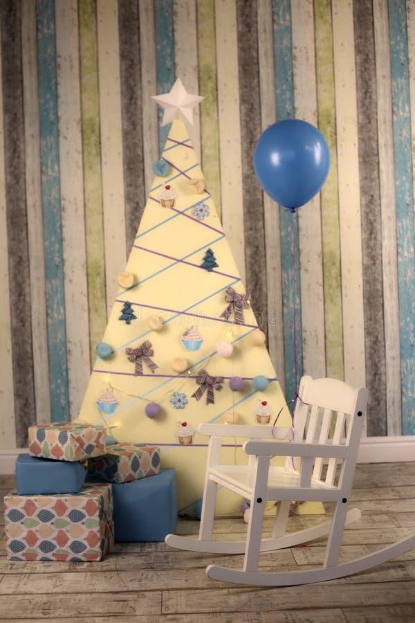 Interior de la decoración de la Navidad con los presentes del árbol y la mecedora del bebé fotografía de archivo libre de regalías