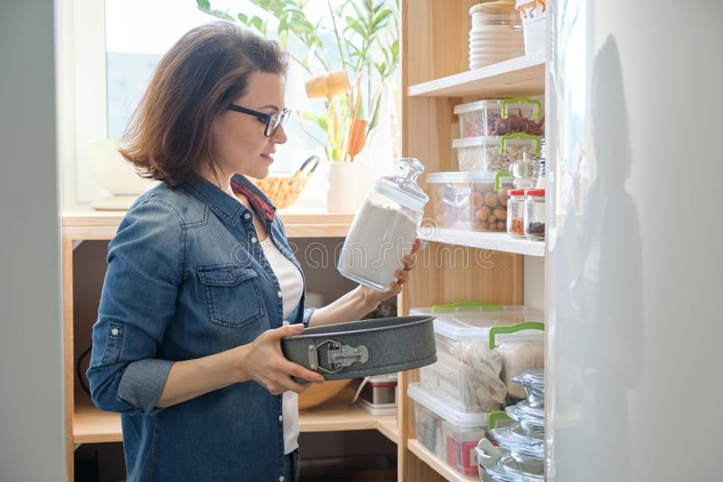 Interior de la despensa de madera con los productos para cocinar Mujer adulta que toma el art?culos de cocina y la comida imagen de archivo