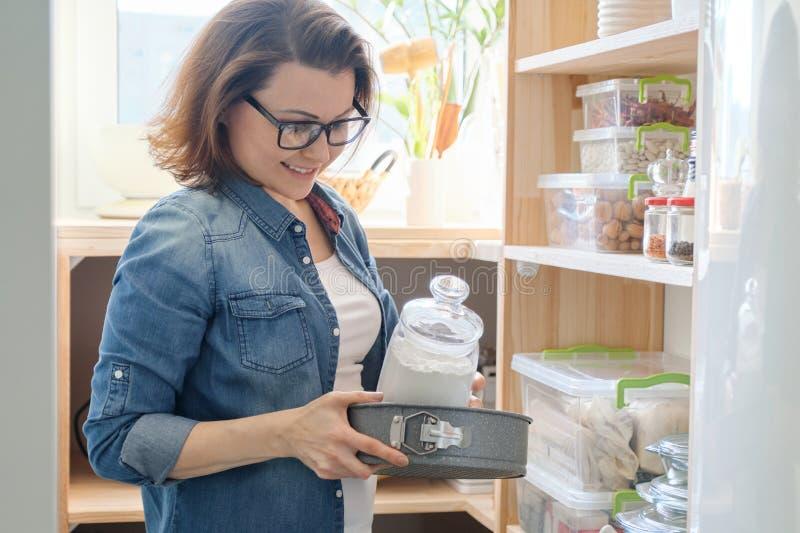 Interior de la despensa de madera con los productos para cocinar Mujer adulta que toma el art?culos de cocina y la comida fotografía de archivo libre de regalías