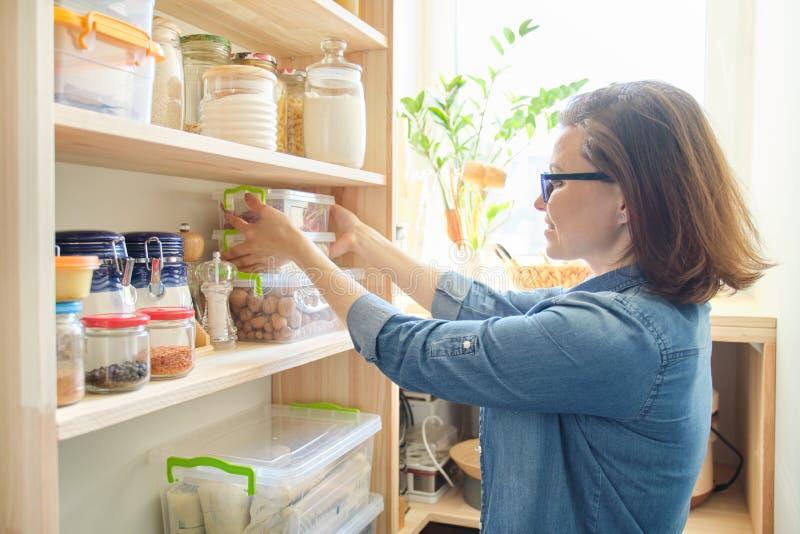 Interior de la despensa de madera con los productos para cocinar Mujer adulta que toma el art?culos de cocina y la comida de los  imagen de archivo