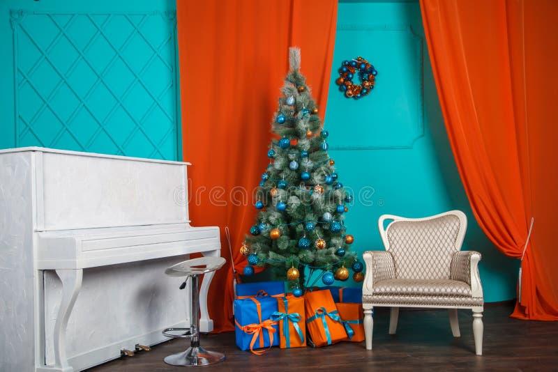 Interior de la Navidad con el piano blanco Colores anaranjados y azules fotos de archivo