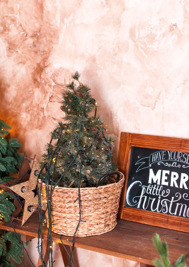 Interior de la Navidad del estilo del desván con el pequeño árbol de abeto en cesta de mimbre foto de archivo libre de regalías