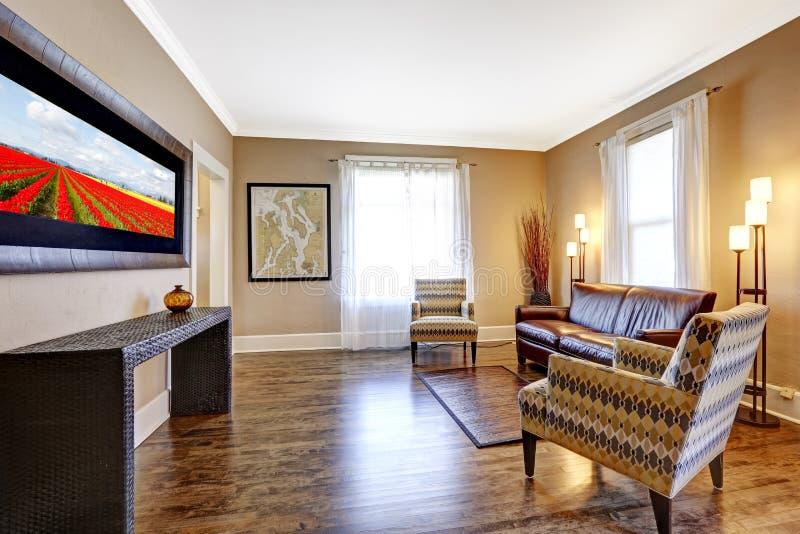 Interior de la sala de estar con el sofá de cuero y dos sillas fotografía de archivo