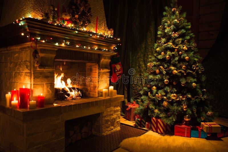 Interior de la sala de estar con la chimenea y el árbol de navidad adornados fotos de archivo libres de regalías