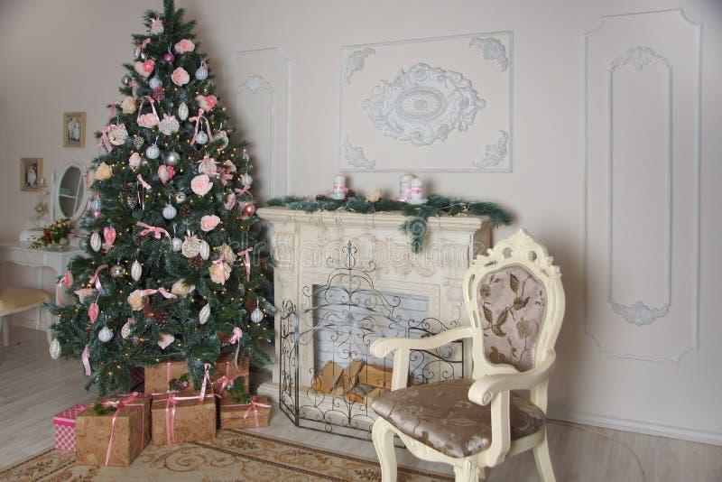 Interior de la sala de estar con una chimenea, adornado por el Año Nuevo con un árbol de navidad grande y las porciones de presen imágenes de archivo libres de regalías