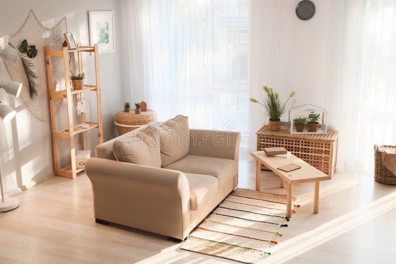 Interior de la sala de estar en estilo del eco con el sofá cómodo y las plantas verdes fotografía de archivo