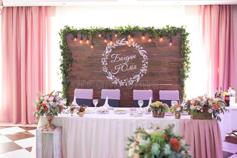 Interior de la tabla de los recienes casados en restaurante con la decoración natural: flores frescas y guirnaldas retras imagen de archivo libre de regalías