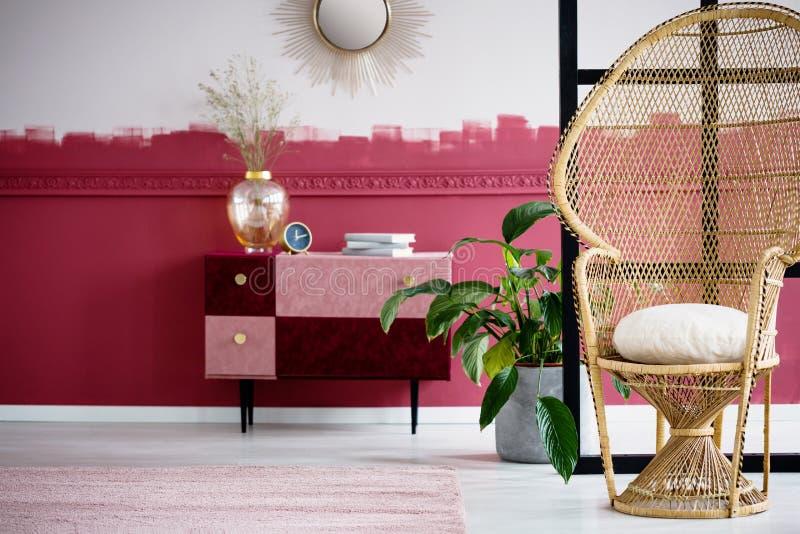 Interior de moda de la sala de estar con la silla de mimbre del pavo real y el rosa en colores pastel hecho a mano y el pecho de  foto de archivo libre de regalías